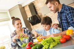 Rodzina stoi w kuchnia szczęśliwych rodzicach patrzeje po syna ciie dzwonkowego pieprzu należnie wpólnie w domu obraz royalty free