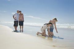 Rodzina target475_0_ przy skorupę na plaży Zdjęcia Royalty Free