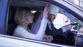 Rodzina transportu zakup, młodego klienta rodzina z dziecko dziewczyną ostrożnie rozważa auto wewnętrznego obsiadanie wśrodku sal zbiory