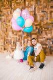 Rodzina trzy świętuje córki ` s urodziny jeden rok wśrodku izbowego obsiadania na podłoga przeciw tłu drewniany Fotografia Stock