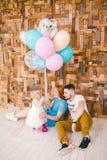 Rodzina trzy świętuje córki ` s urodziny jeden rok wśrodku izbowego obsiadania na podłoga przeciw tłu drewniany Zdjęcie Royalty Free