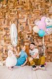 Rodzina trzy świętuje córki ` s urodziny jeden rok wśrodku izbowego obsiadania na podłoga przeciw tłu drewniany Obrazy Stock