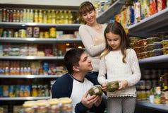 Rodzina trzy kupuje konserwować jedzenie Zdjęcie Stock
