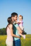 Rodzina trzy ludzie ma zabawę outside Ojciec trzyma jej li Obrazy Royalty Free