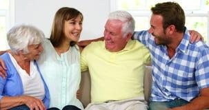 Rodzina trzyma each inny i ono uśmiecha się na kanapie zbiory wideo