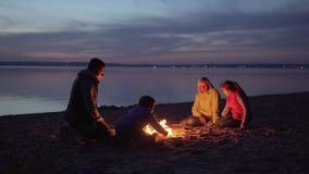 Rodzina tury?ci odpoczywa przy ogniskiem na nocy pla?y zdjęcie wideo