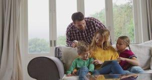 Rodzina używa cyfrową pastylkę na kanapie w wygodnym domu 4k zbiory