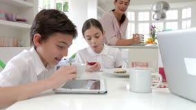 Rodzina Używa Cyfrowych przyrząda Przy Śniadaniowym stołem zbiory