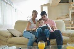 Rodzina używa pastylka komputer w domu Zdjęcie Royalty Free