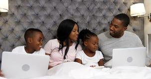 Rodzina używa urządzenia elektroniczne w sypialni 4k zdjęcie wideo