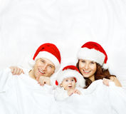 Rodzina w Bożenarodzeniowym kapeluszu, dziecko dzieciaku, matce i ojcu na bielu, zdjęcie royalty free