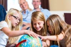 Rodzina w domu dzieci bawić się z kulą ziemską Fotografia Royalty Free