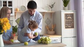 Rodzina w kuchni, c?rka jest w jej r?kach, dok?d tata siedzi jego c?rki na stole, i mama stoi w pobli?u zbiory wideo