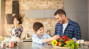 Rodzina w kuchni i syn pozycji ma zabawę radosną w domu wpólnie ojcuje podczas gdy macierzysty opowiadać na smartphone patrze fotografia stock
