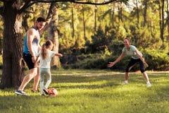 Rodzina w parkowym bawić się futbolu Kobieta bawić się jako bramkarz Fotografia Stock