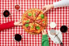 Rodzina w włoskich obywatelów kolorów ubraniach bierze kawałki pizza Obrazy Stock