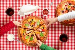 Rodzina w włoskich obywatelów kolorów ubraniach bierze kawałki pizza Fotografia Stock