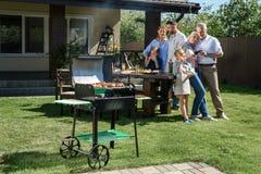 Rodzina wydaje czas wpólnie podczas gdy mieć grilla z grillem przy jardem zdjęcia royalty free