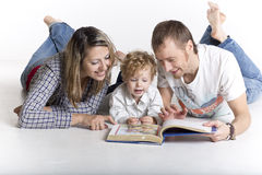 Rodzina z berbeciem czyta książkę na podłoga Fotografia Stock