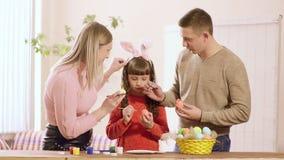 Rodzina z córką, dom dekoruje Wielkanocnych jajka na stole jest farbą i koszem jajka zbiory