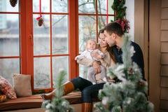 Rodzina z chłopiec obsiadaniem blisko okno w domu dekorował dla bożych narodzeń Zdjęcie Royalty Free