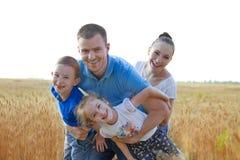 Rodzina z dwa dzieciakami ma zabawę wśród pszenicznego pola Fotografia Stock