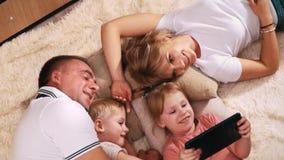 Rodzina z dwa małymi dziećmi kłama na ciepłej koc i ono uśmiecha się patrzejący pastylkę która trzyma jej córki, tata zdjęcie wideo