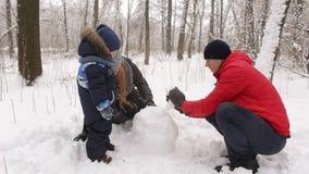Rodzina z dziećmi buduje bałwanu w parku zbiory wideo