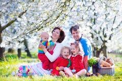 Rodzina z dziećmi cieszy się pinkin w wiosna parku Fotografia Royalty Free