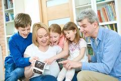 Rodzina z dziećmi dyskutuje ultradźwięku obrazu cyfrowego wizerunek w domu Obrazy Stock