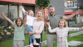 Rodzina Z dziećmi Patrzeje kamery pozycję Na ulicie Outdoors Para I dzieciaki Kupuje Nowego dom Real Estate właściciele zdjęcie wideo