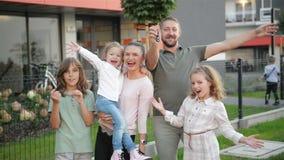 Rodzina Z dziećmi Patrzeje kamery pozycję Na ulicie Outdoors Para I dzieciaki Kupuje Nowego dom Real Estate właściciele zbiory