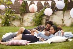 Rodzina Z dzieckiem Relaksuje Na dywaniku W ogródzie Wpólnie Zdjęcie Stock