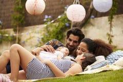 Rodzina Z dzieckiem Relaksuje Na dywaniku W ogródzie Wpólnie Zdjęcia Stock