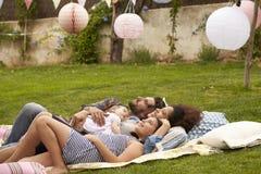 Rodzina Z dzieckiem Relaksuje Na dywaniku W ogródzie Wpólnie Obrazy Stock
