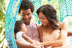 Rodzina Z dzieckiem Relaksuje Na Plenerowej ogród huśtawce Seat zdjęcia royalty free