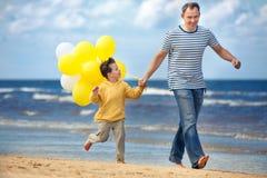 Rodzina z kolorem żółtym szybko się zwiększać bawić się na plaży Obrazy Stock