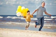 Rodzina z kolorem żółtym szybko się zwiększać bawić się na plaży Zdjęcie Royalty Free