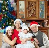 Rodzina z małą dziewczynką w Santa kapeluszach w bożych narodzeniach Zdjęcie Royalty Free