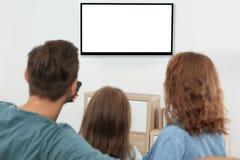 Rodzina z pilota do tv obsiadaniem na leżance TV w domu i dopatrywaniu, przestrzeń dla projekta na ekranie obraz royalty free