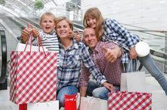 Rodzina z torba na zakupy w centrum handlowym pokazuje kciuki Zdjęcia Stock