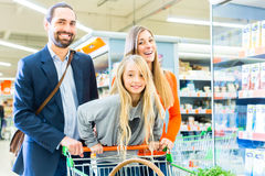 Rodzina z wózek na zakupy w supermarkecie Zdjęcia Stock