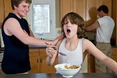 Rodzinna śniadaniowa zabawa - nastoletni bracia ma zboża: szczerzy strzały zdjęcie stock