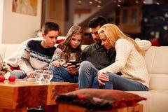 Rodzinna bawić się gra na telefonie komórkowym na Bożenarodzeniowych wakacjach Zdjęcie Stock