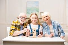 Rodzinna bawić się jenga gra wpólnie i ono uśmiecha się przy kamerą Obraz Stock