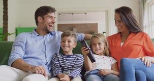 Rodzinna dopatrywanie telewizja wp?lnie w domu w ?ywym pokoju 4k zdjęcie wideo