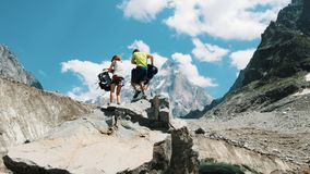 Rodzinna para turyści z plecakami w podwyżce usuwać plecaki na wierzchołku w górach fotografia royalty free
