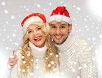 Rodzinna para w pulowerach i Santa kapeluszach Zdjęcie Royalty Free