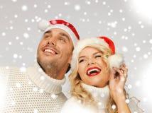 Rodzinna para w pulowerach i Santa kapeluszach Obrazy Stock