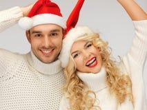 rodzinna para w pulowerach i Santa kapeluszach Zdjęcie Stock